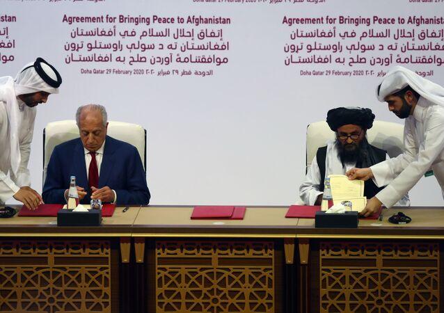 Mullah Abdul Ghani Baradar, il leader della delegazione talebana, firma l'accordo con Zalmay Khalilzad, l'inviato per la pace Usa in Afghanistan, il 29 febbraio del 2020