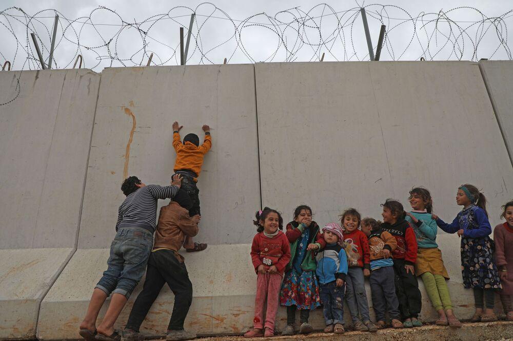 I bambini siriani cercano di scavalcare il muro del confine turco nella provincia nord-occidentale di Idlib in Siria