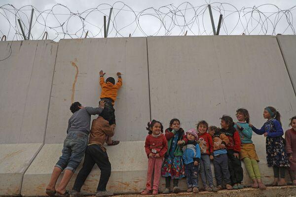 I bambini siriani cercano di scavalcare il muro del confine turco nella provincia nord-occidentale di Idlib in Siria - Sputnik Italia