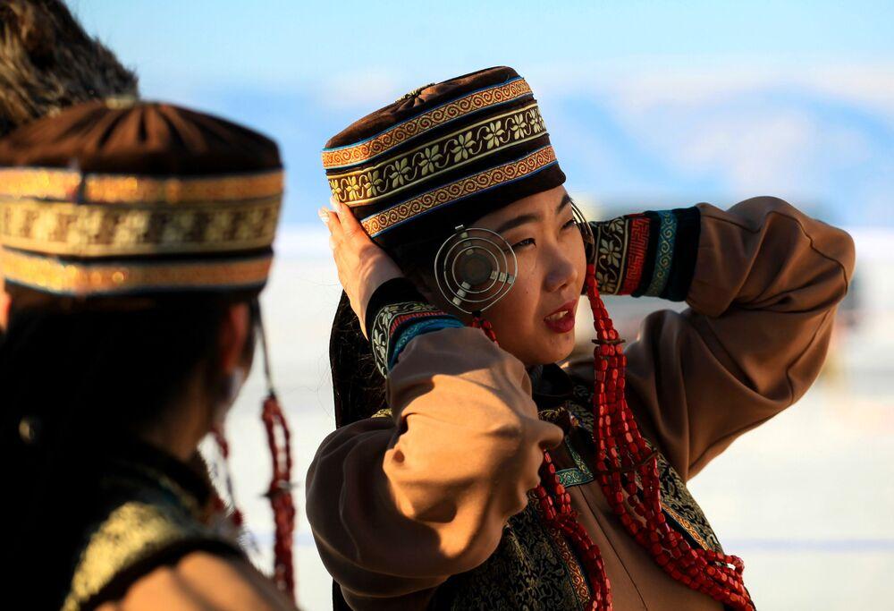 Una giovane donna indossa un abito tradizionale al concorso internazionale di sculture di ghiaccio Olkhon Ice Fest sul lago di Baikal, Russia