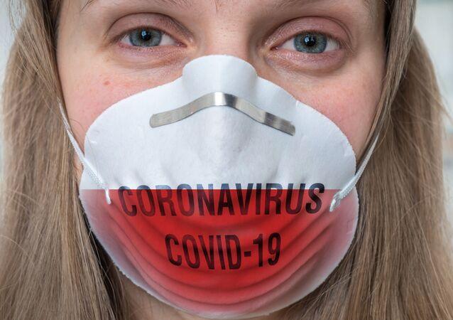 Una donna copre il proprio volto con una mascherina