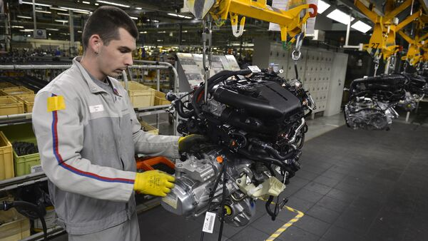 An employee works on the engine assembly line of the Peugeot 208 car by French car maker PSA Peugeot Citroen at the company's automobile factory in Trnava, western Slovakia - Sputnik Italia