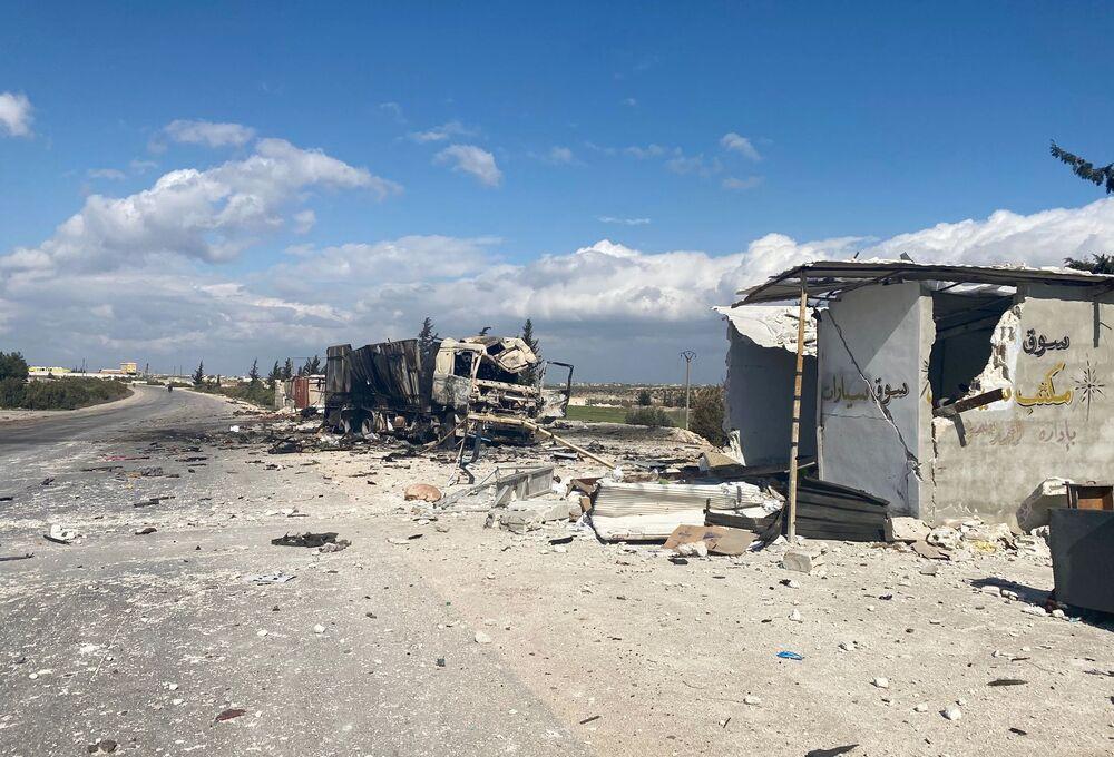 Un veicolo militare siriano distrutto e le case a Saraqib nella provincia di Idlib in Siria.