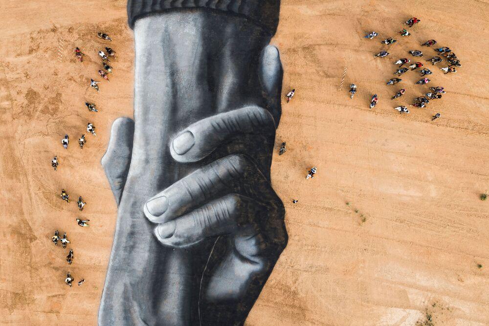 Motociclisti intorno al land art dell'artista Saype in Burkina Faso.