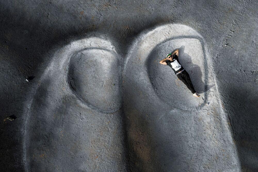 L'artista franco-svizzero Saype posa su un frammento del suo dipinto gigantesco biodegradabile al Monumento degli eroi a Ouagadougou in Burkina Faso. L'affresco lungo 200 metri copre uno spazio di circa 5000 mq. Questa opera è il quinto passo del progetto Beyond Walls (Oltre i muri).