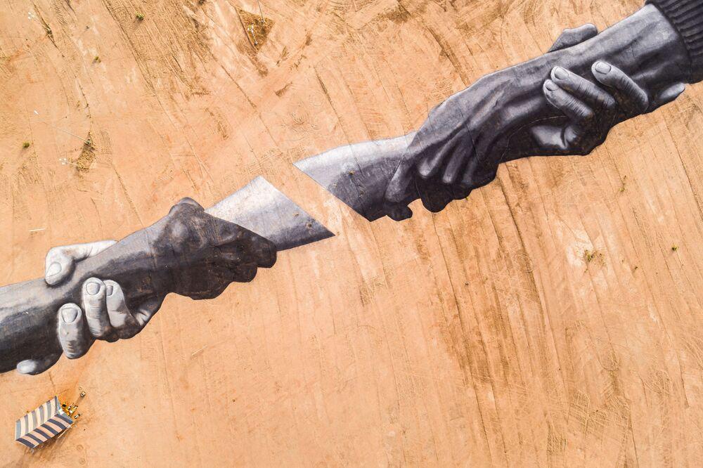 Un land art al Monumento degli eroi a Ouagadougou in Burkina Faso. L'affresco lungo 200 metri copre uno spazio di circa 5000 mq. Questa opera è il quinto passo del progetto Beyond Walls (Oltre i muri).