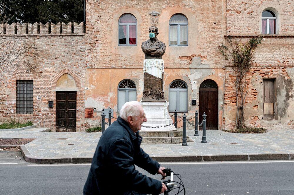 La vita dentro la zona rossa: un pensionato senza mascherina passa in bicicletta davanti una statua con la faccia coperta con una mascherina con la scritta F**k virus a San Fiorano, chiusa per l'epidemia del coronavirus.