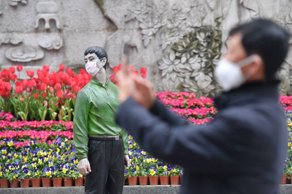 Un uomo fotografa una statua in mascherina a Pechino.