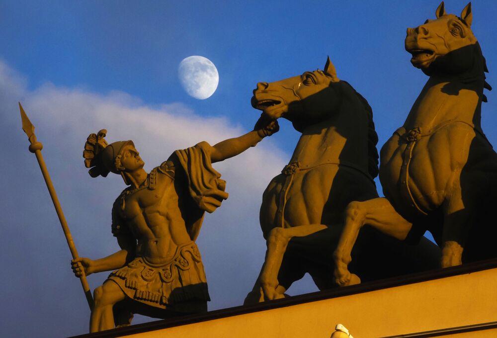 La luna sopra una scultura in Piazza Dvortsovaya a San Pietroburgo, Russia, il 6 marzo 2020