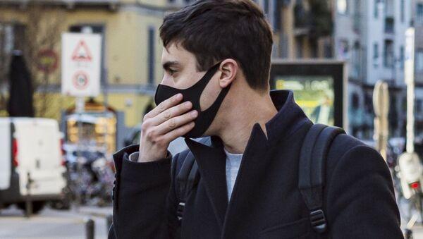 Un uomo in mascherina a Milano - Sputnik Italia