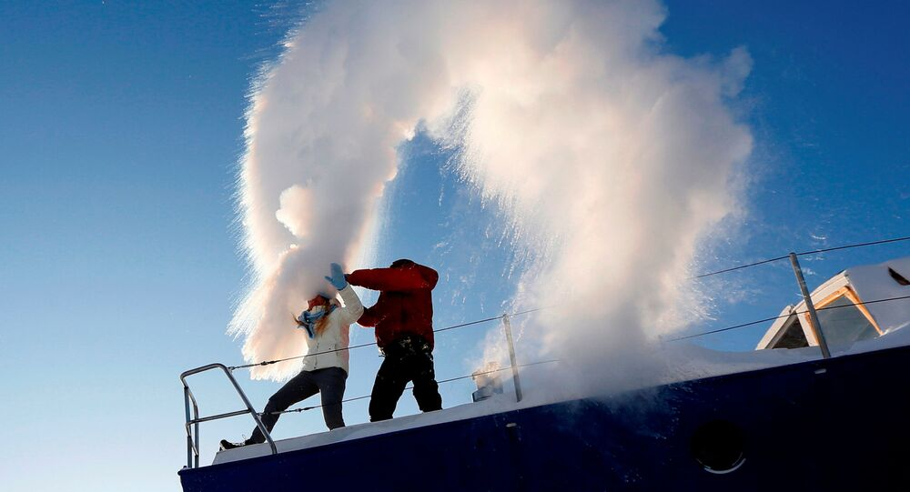 People throw hot water into the air, with the air temperature at about minus 34 degrees Celsius (minus 29.2 degrees Fahrenheit), outside Krasnoyarsk, Russia, January 22, 2018.