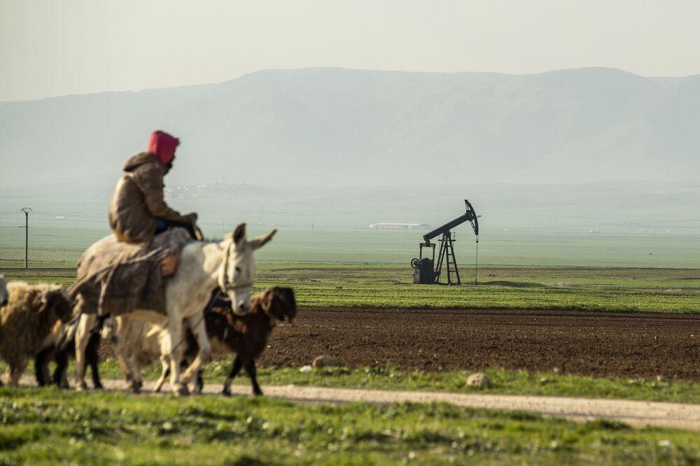 Un pastore cavalca un asino vicino a un giacimento di petrolio in Siria al confine con la Turchia.