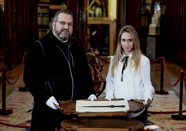Padre Serafino Jamourlian e Vittoria Dall'Armellina mostrano la spada conservata nel museo dell'isola