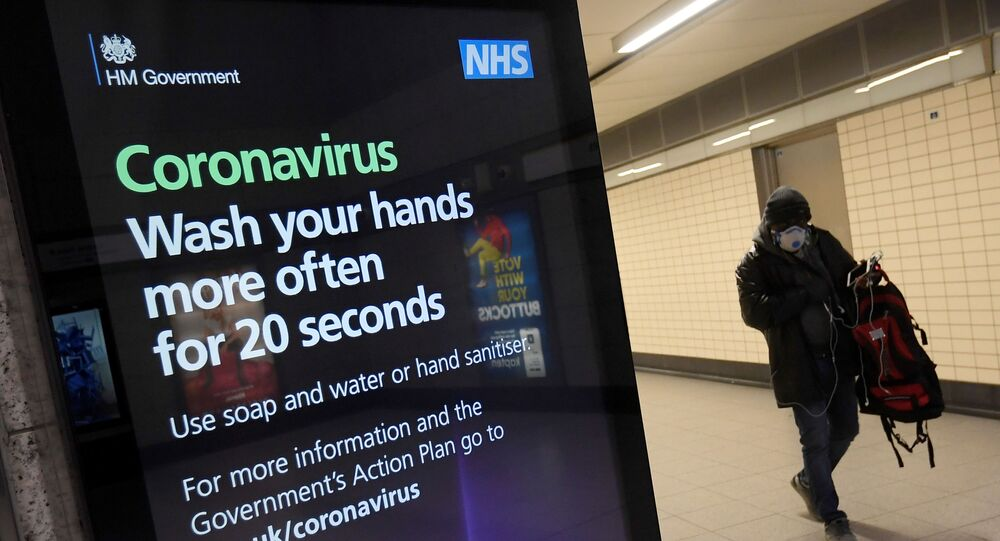 Un uomo con una maschera protettiva cammina davanti a una pubblicità della campagna sanitaria del governo britannico alla stazione della metropolitana di Victoria