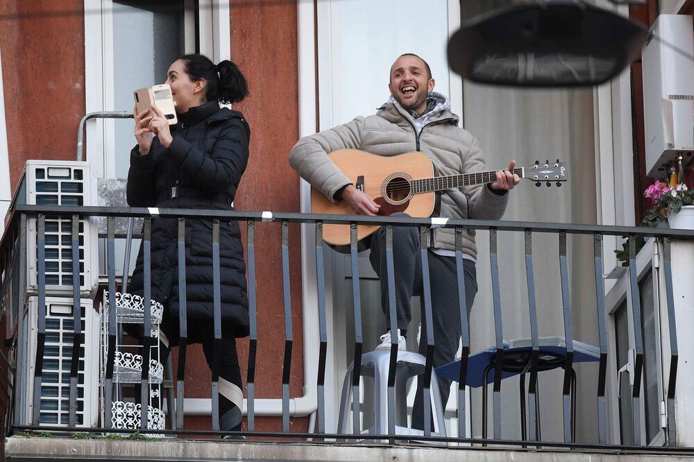 Un uomo suona la chitarra dal suo balcone durante il sesto giorno di quarantena a Milano, Italia, 15 marzo 2020