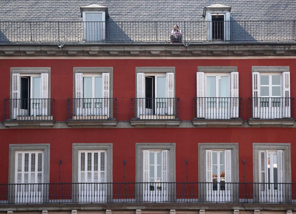 Una donna sul tetto della sua casa in Plaza Mayor in quarantena per l'epidemia del coronavirus a Madrid, Spagna, il 15 marzo 2020