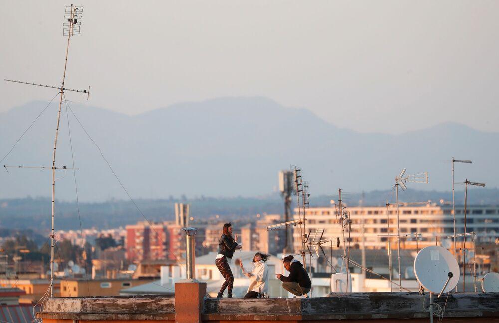 Le ragazze sul tetto della loro casa in quarantena per l'epidemia del coronavirus a Roma, Italia, il 15 marzo 2020