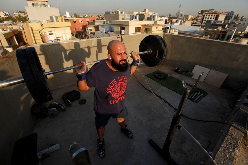 Osama Hussein si allena sul tetto della sua casa, mentre le palestre chiuse come misura preventiva contro il coronavirus a Erbil, Iraq, l'11 marzo 2020