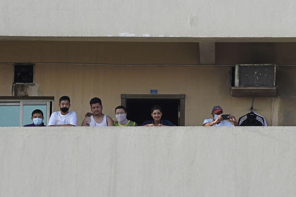 Lavoratori stranieri sul balcone di un edificio in cui un residente è risultato positivo al coronavirus (COVID-19) nella zona industriale di Manama, Bahrain, il 13 marzo 2020