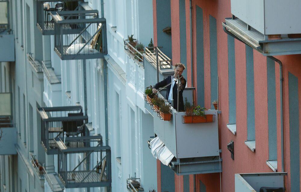 Un uomo suona il violino dal suo balcone a Berlino, Germania, il 15 marzo 2020