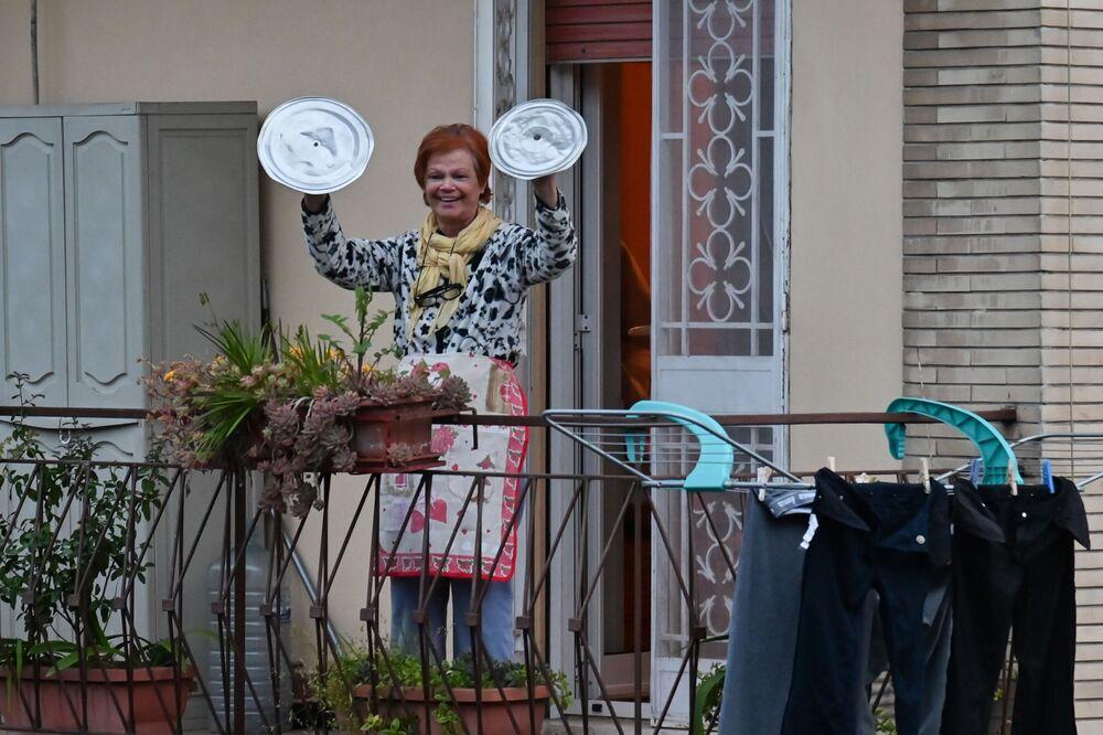 Una donna partecipa al flash mob Affacciati alla Finestra, Roma Mia! durante la quarantena a Roma, Italia, il 13 marzo 2020