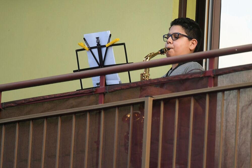 Un ragazzo suona il sassofono dal suo balcone a Milano, Italia, il 14 marzo 2020