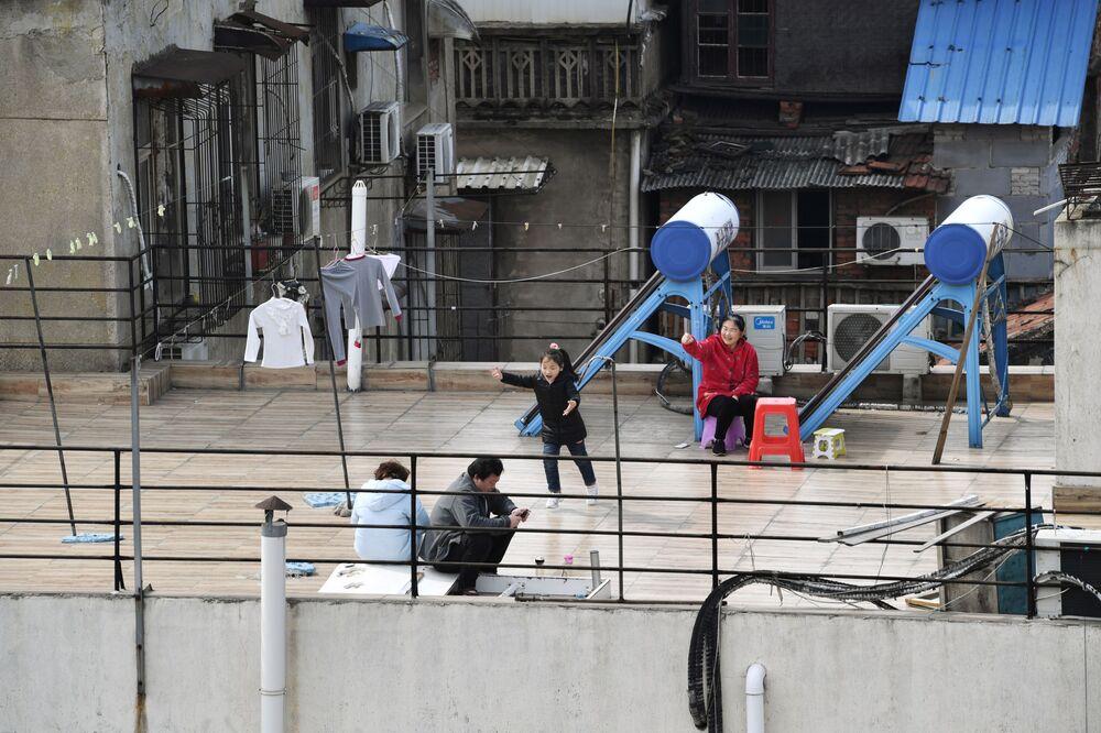 Un bambino gioca accanto agli adulti seduti sulla terrazza sul tetto di un edificio in un complesso residenziale a Wuhan, l'epicentro del nuovo focolaio del coronavirus (COVID-19), provincia di Hubei, Cina, il 4 marzo 2020