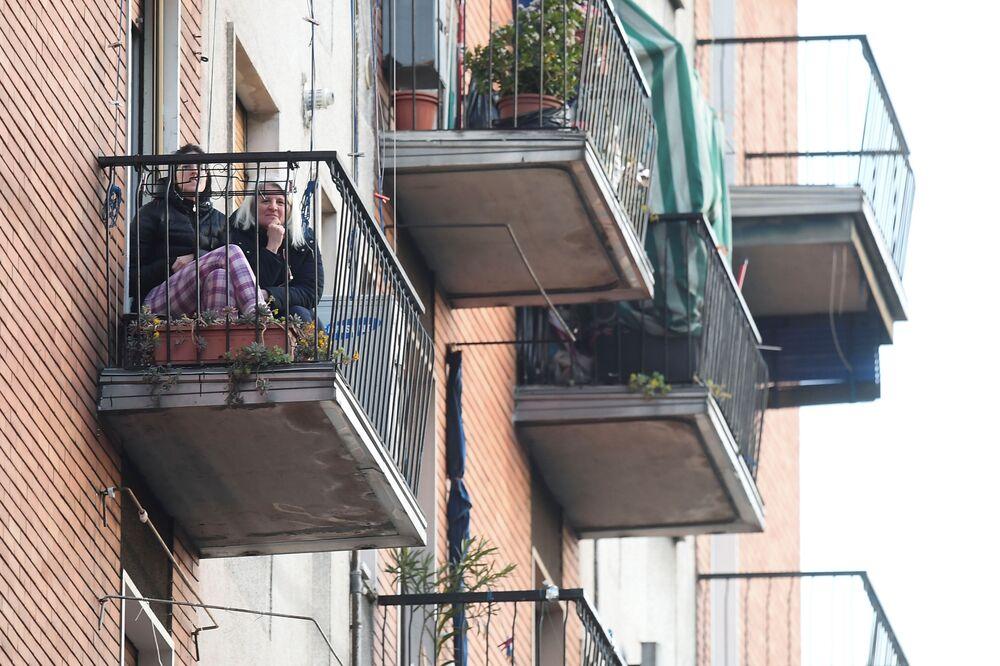 Le donne ascoltano la musica mentre un vicino suona la chitarra dal suo balcone a Milano, Italia, il 15 marzo 2020