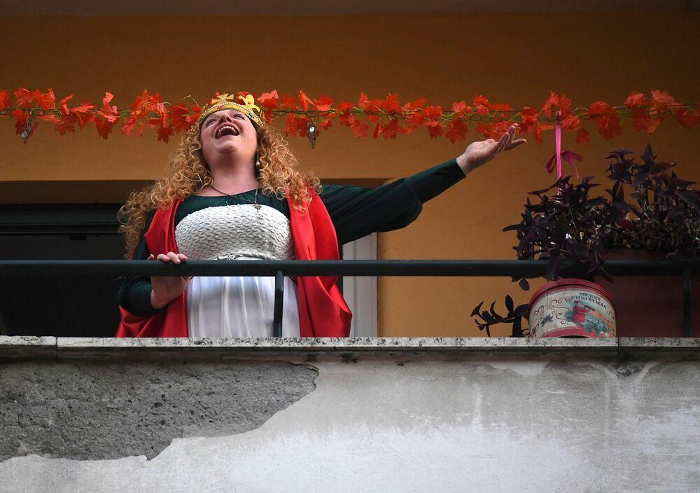 Una donna canta dal suo balcone per la quarantena imposta tra le misure restrittive per combattere l'epidemia di coronavirus, Roma, Italia, il 14 marzo 2020