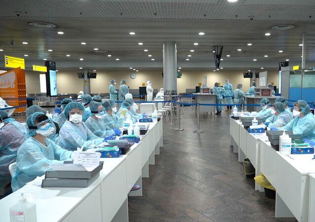 Il personale medico si prepara a controllare i passeggeri all'aeroporto Sheremetyevo nei pressi di Mosca, Russia