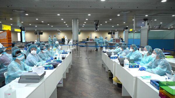 Il personale medico si prepara a controllare i passeggeri all'aeroporto Sheremetyevo nei pressi di Mosca, Russia - Sputnik Italia