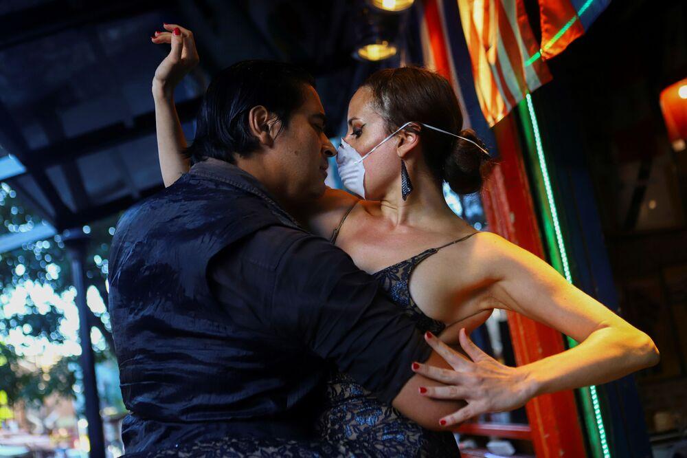 Una coppia in mascherina balla in un ristorante quasì vuoto a Buenos Aires, Argentina.