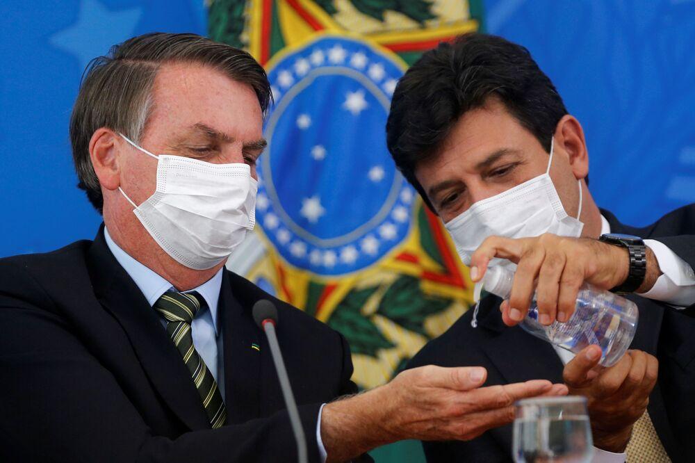 Il presidente brasiliano Jair Bolsonaro e il ministro della Sanità Henrique Mandettas in mascherina si disinfettano le mani durante una conferenza in Brasile.