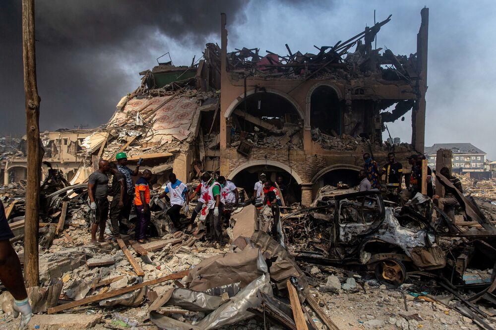 I rappresentanti della Croce Rossa portano via una vittima dell'esplosione del gas in un edificio a Lagos, Nigeria.
