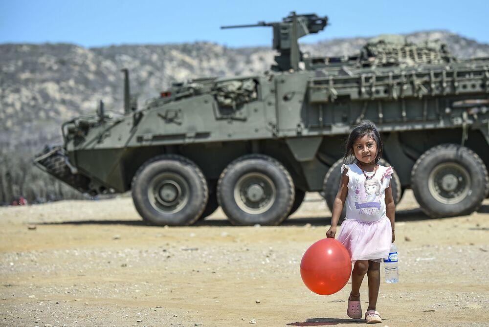 Una ragazza con un palloncino rosso vicino a un carro armato in Colombia.