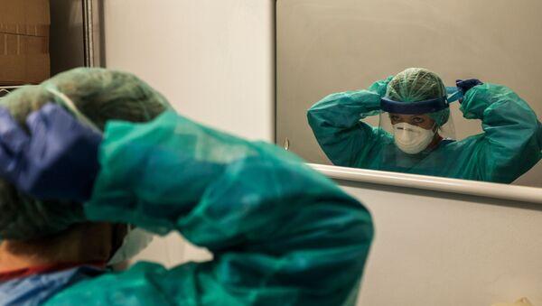 Un'infermiera all'inizio di un turno il 12 marzo 2020 all'ospedale di Cremona, Italia - Sputnik Italia
