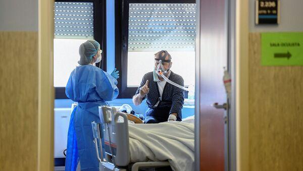 Un medico con un paziente contagiato dal coronavirus in un'unità di terapia intensiva presso l'ospedale Oglio Po di Cremona, Italia - Sputnik Italia