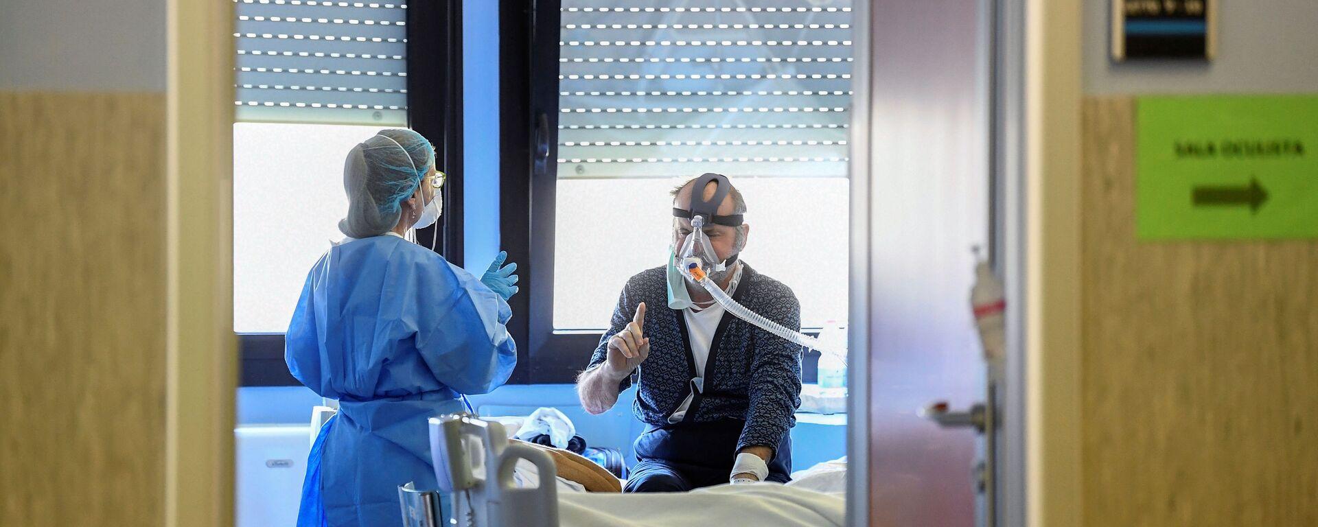 Un medico con un paziente contagiato dal coronavirus in un'unità di terapia intensiva presso l'ospedale Oglio Po di Cremona, Italia - Sputnik Italia, 1920, 27.08.2021