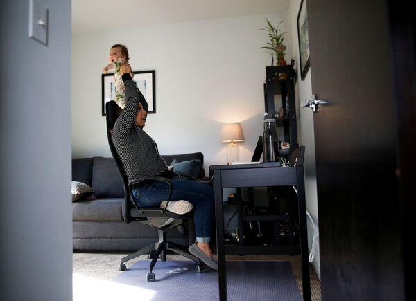 Teresa Mosqueda gioca con sua figlia neonata Camila Valdes-Mosqueda mentre partecipa a una riunione del consiglio di Seattle per telefono a causa della quarantena per l'epidemia del coronavirus (COVID-19) a Seattle, Washington, USA, il 23 marzo 2020  - Sputnik Italia