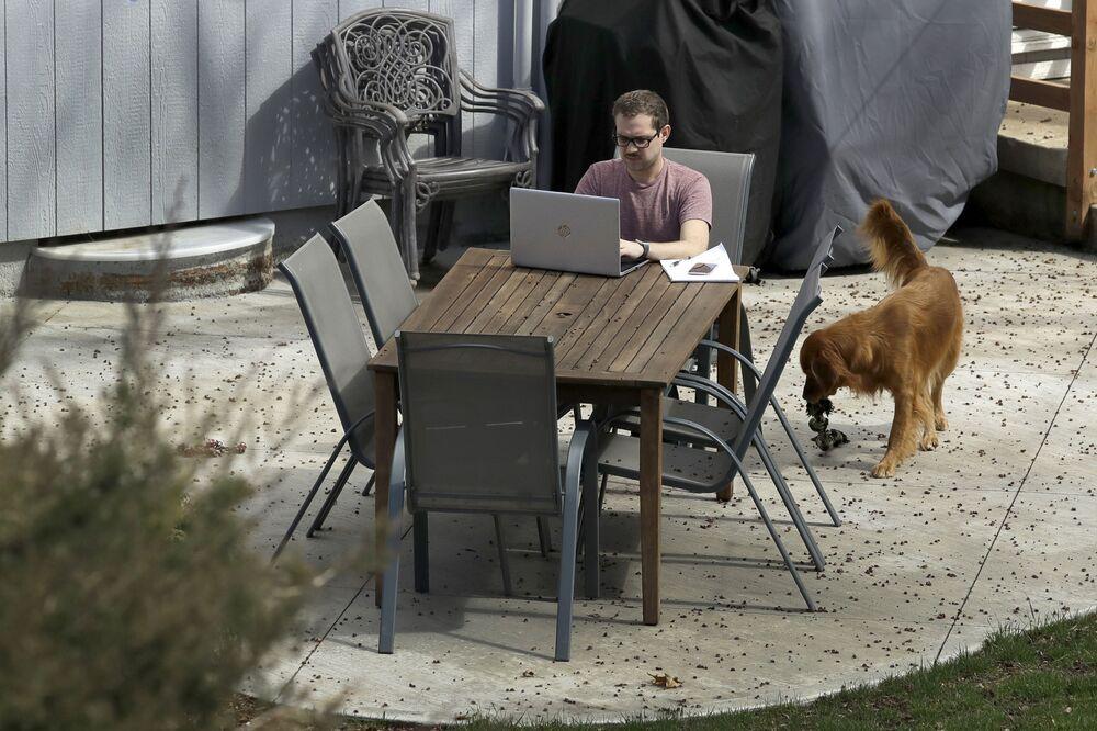 Erik Wray lavora al suo computer nel cortile di casa sua, USA, il 19 marzo 2020