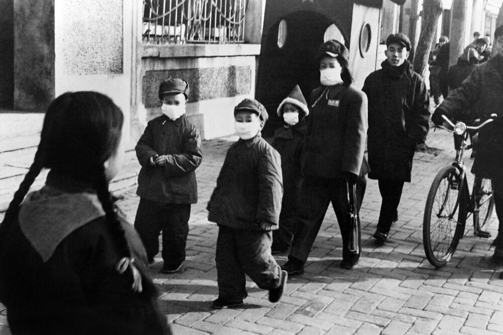Le persone in maschere protettive per le strade di Pechino, Cina, 1954