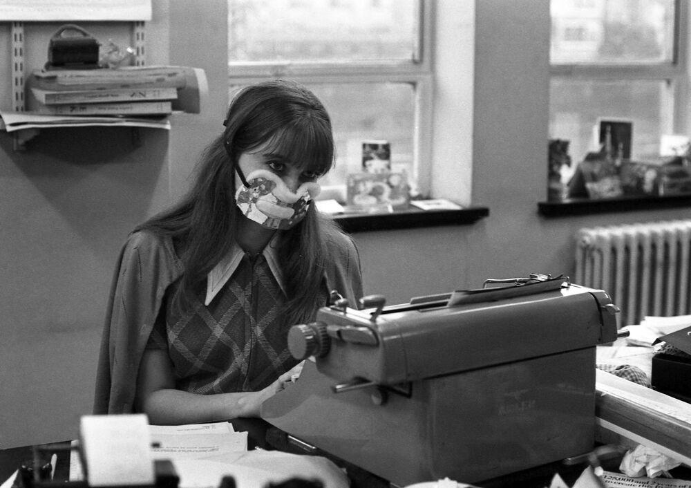 Una segretaria con una maschera protettiva in un ufficio di Londra durante l'epidemia di influenza, 1970