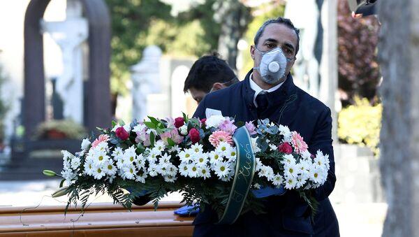 Сотрудник похоронного агентства в медицинской маске во время транспортировки гроба с телом умершего от коронавируса в городе Бергамо, Италия - Sputnik Italia