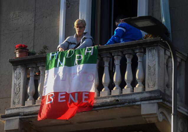 Una donna vista sul balcone con la bandiera italiana con la scritta tutto andrà bene a Milano