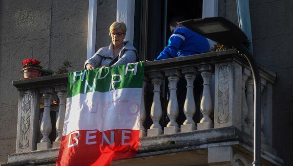 Una donna vista sul balcone con la bandiera italiana con la scritta tutto andrà bene a Milano - Sputnik Italia