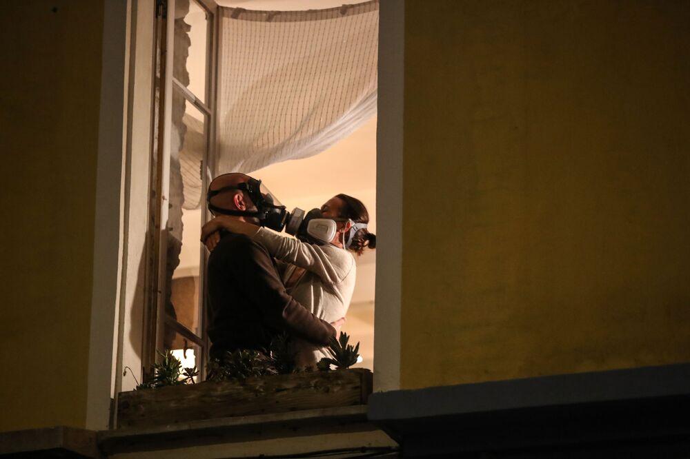 Una coppia in mascherina si bacia in finestra in un palazzo a Nizza, Francia.