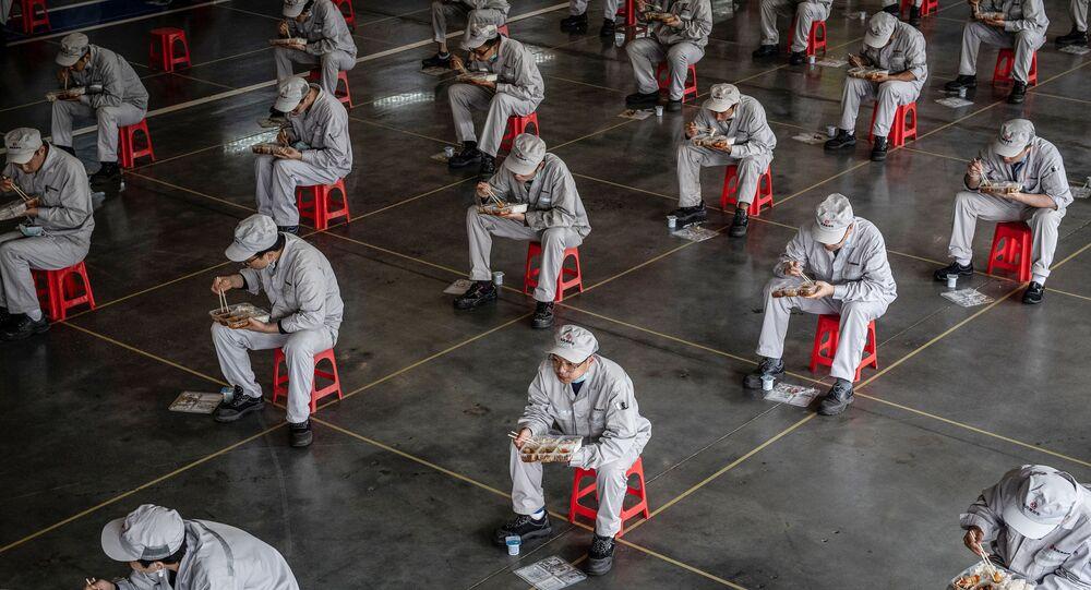 Gli operai durante l'intervallo di pranzo alla fabbrica di automobili di Dongfeng Honda a Wuhan, Cina.