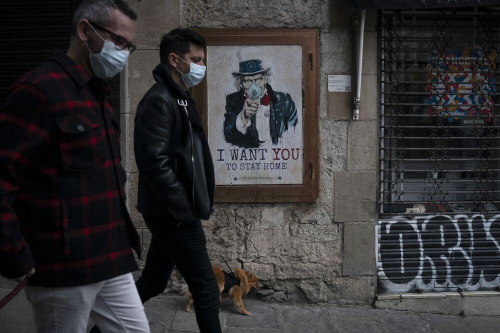 La gente per vie di Barcellona sullo sfondo del poster dall'artista TvBoy