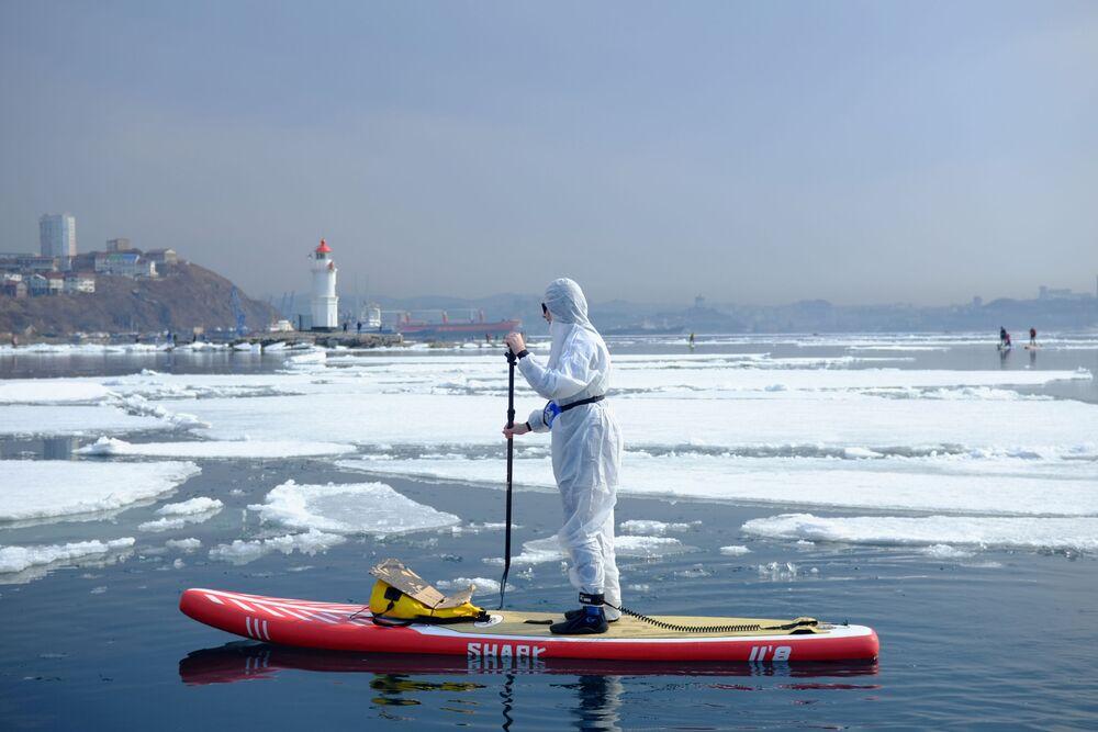 Un amante dello stand up paddle in tuta protettiva nella baia di Vladivostok, Russia.