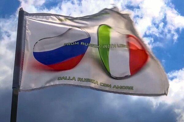 Le bandiere italiana e russa su un camion della colonna dei mezzi speciali del ministero della Difesa russo prima della marcia dalla base aerea italiana Pratica di Mare - Sputnik Italia